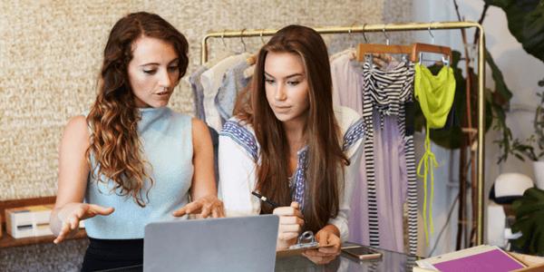 Socias de negocio de ropa revisando stock
